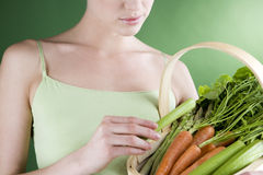 A young woman holding a basket full of vegetables, close-up Stock Image