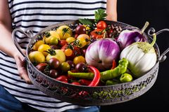 Young woman holding a basket full of veggies Royalty Free Stock Images