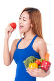 Young woman holding basket of vegetables. Stock Photo