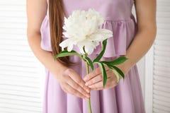 Young woman holding beautiful peony flower Stock Photo