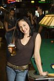 Young woman holding beer. Portrait of young caucasian woman holding beer beside billiards table in pub stock images