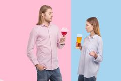 Young woman holding beer and looking at husbands wine disgustingly. Awful drink. Petite young women holding a glass of beer and looking at the wine in her Stock Photography