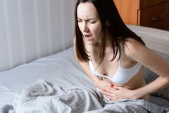 Young woman holding belly sitting in bed suffering from pain during menstruation Stock Photo