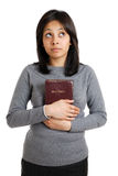 Young woman holding a bible whilst looking up Stock Images
