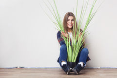Young woman holding big green plant sitting against wall. Royalty Free Stock Photo