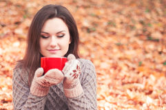Young woman holding a big red cup and smelling tea Royalty Free Stock Photos