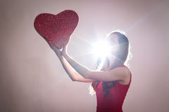 A young woman holding a big red heart against the ligth Stock Photos