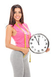 Young woman holding a big wall clock Stock Images