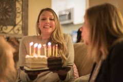 Young woman holding birthday cake with glowng candles stock photography