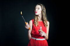 Young woman holding birthday cupcake and lighter Stock Photo