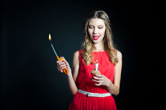 Young woman holding birthday cupcake and lighter Stock Photography