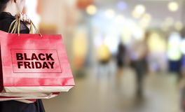 Young woman holding black friday shopping bag. At department store royalty free stock photos
