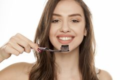 Active charcoal tooth paste. Young woman holding a black tooth brush with black tooth paste with active charcoal on a white background stock photo