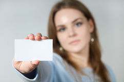 Young woman holding blank business card. Young Woman holding a business card in her hands Royalty Free Stock Image