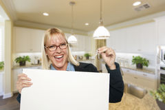 Young Woman Holding Blank Sign and Keys Inside Kitchen. Happy Young Woman Holding Blank Sign and Keys Inside Beautiful Custom Kitchen Royalty Free Stock Image
