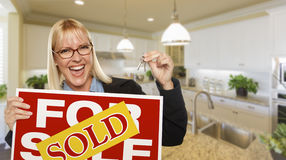 Young Woman Holding Blank Sign and Keys Inside Kitchen. Happy Young Woman Holding Sold For Sale Real Estate Sign and Keys Inside Beautiful Custom Kitchen Royalty Free Stock Photos
