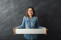 Young woman holding blank white banner. Amazed young woman holding white blank banner. Excited girl showing paper sheet for sales advertisement, copy space Royalty Free Stock Photography