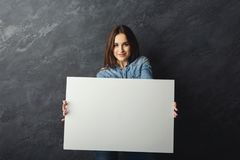 Young woman holding blank white banner. Happy young woman holding white blank banner. Excited girl showing paper sheet for sales advertisement, copy space Stock Photos