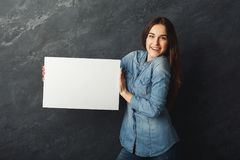 Young woman holding blank white banner. Happy young woman holding white blank banner. Excited girl showing paper sheet for sales advertisement, copy space Stock Image