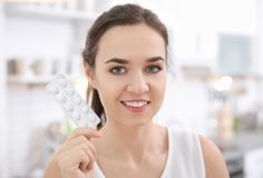 Young woman holding blister with vitamin pills. Indoors Royalty Free Stock Photos