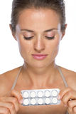 Young woman holding blistering package of pills Stock Image