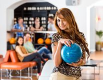Young Woman Holding Blue Bowling Ball in Club Stock Photo