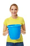 Young woman holding blue bucket. Stock Photo