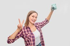 Young woman holding blue camera in hand and stretch arm up. She poses and smiles. Woman looks straight. She shows piece stock photography