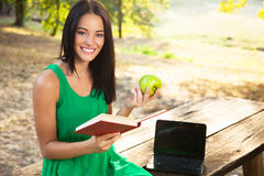 Young woman holding book and apple Stock Photos
