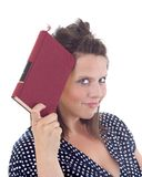 Young woman holding a book to her head Royalty Free Stock Photography