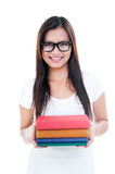 Young Woman Holding Books. Portrait of a beautiful young woman in eyeglasses and holding books over white background Royalty Free Stock Photo