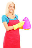 Young woman holding a bottle of cleaning solution Royalty Free Stock Photo