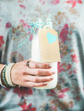 Young woman holding bottle of dairy-free almond milk in hand Stock Images