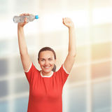 Young  woman holding bottle in hand over her head. Hands up Royalty Free Stock Photo