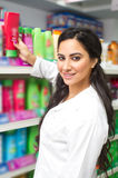 Young woman holding bottle of shampoo in supermarket Royalty Free Stock Photos