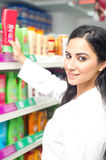 Young woman holding bottle of shampoo in supermarket Royalty Free Stock Images