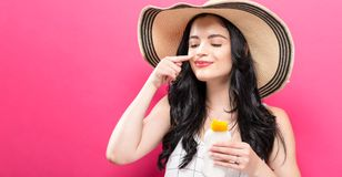 Young woman holding a bottle of sunblock. On a solid background Royalty Free Stock Photography