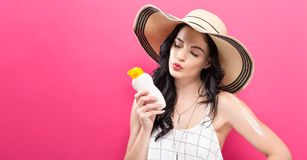 Young woman holding a bottle of sunblock. On a solid background Stock Photography