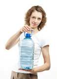 Young woman holding bottle of water. Attractive smiling young woman holding bottle of clear drinking water on white background Royalty Free Stock Image
