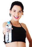 Young woman holding bottle of water. Young fit woman holding bottle of water after fitness exercise Royalty Free Stock Photography