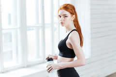 Young woman holding bottle with water in gym Royalty Free Stock Photos