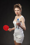 Young woman holding a bottle of water and tennis racquet. Dark background Stock Photos