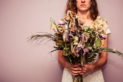 Young woman holding bouquet of dead flowers Stock Image
