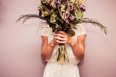 Young woman holding bouquet of dead flowers Royalty Free Stock Photos