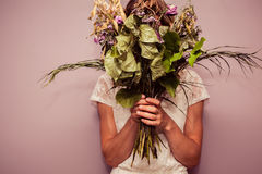 Young woman holding bouquet of dead flowers Stock Photo