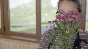 Young woman is holding bouquet of lilac chrysanthemums in hands indoors. stock video footage