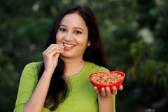 Young woman holding bowl of almonds and eating Stock Image