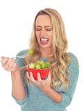 Young Woman Holding a Bowl of Brussels Sprouts Disgusted. A DSLR royalty free image, of attractive healthy young woman, with blonde wavy hair, holding a red bowl royalty free stock photo