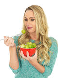 Young Woman Holding a Bowl of Brussels Sprouts. A DSLR royalty free image, of an attractive healthy lifestyle young woman, with long blonde hair, holding a red Stock Photography