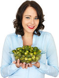 Young Woman Holding a Bowl of Brussels Sprouts Stock Image